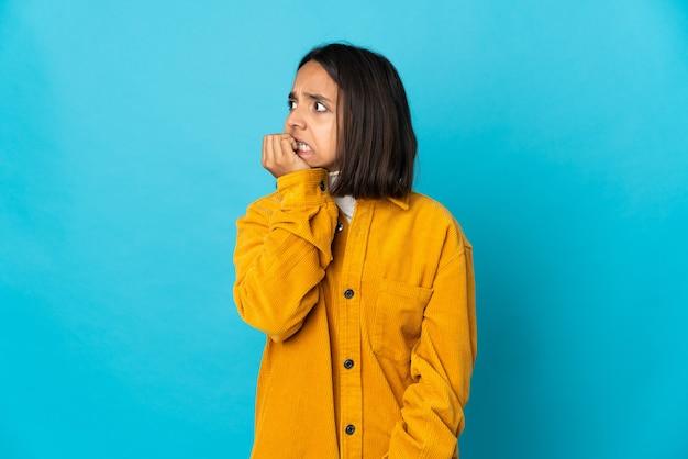 Jeune femme latine isolée sur un mur bleu est un peu nerveuse