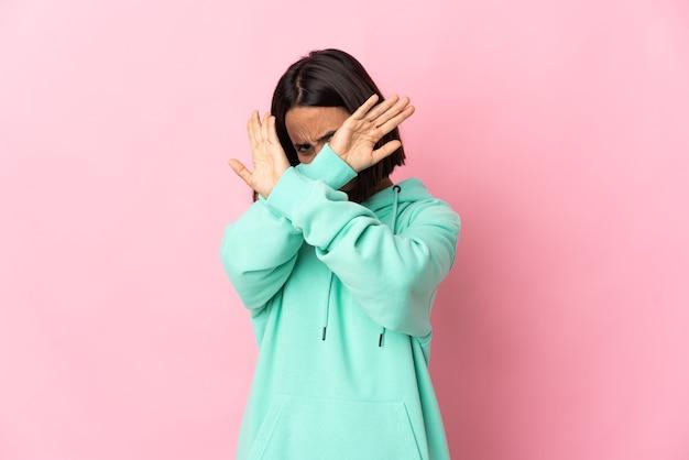 Jeune femme latine isolée sur un mur rose nerveux s'étendant les mains vers l'avant