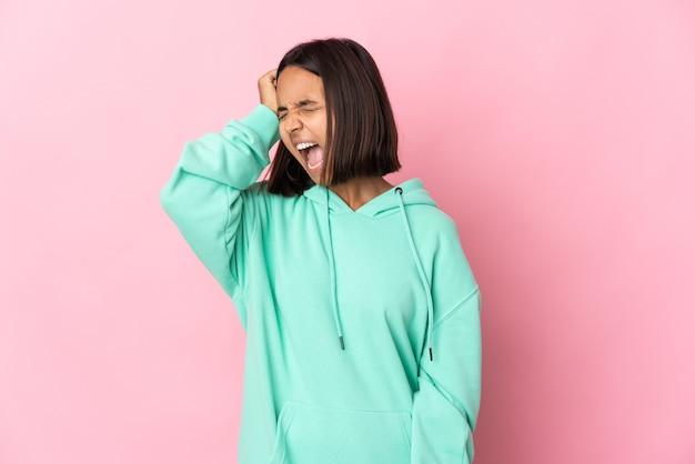 Jeune femme latine isolée sur un mur rose a souligné accablé