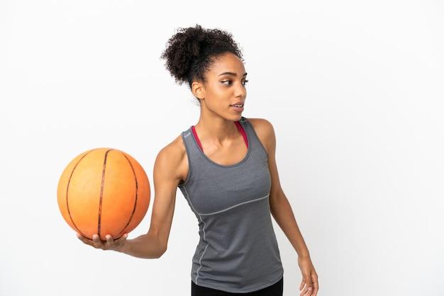 Jeune femme latine de joueur de basket-ball d'isolement sur le fond blanc jouant au basket-ball