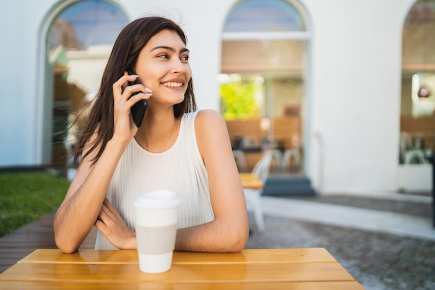 Jeune femme latine parlant au téléphone.