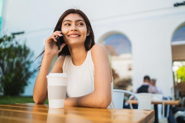 Jeune femme latine, parler au téléphone.