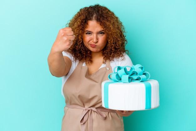 Jeune femme latine pâtisserie tenant un gâteau isolé sur fond bleu montrant le poing à la caméra, expression faciale agressive.