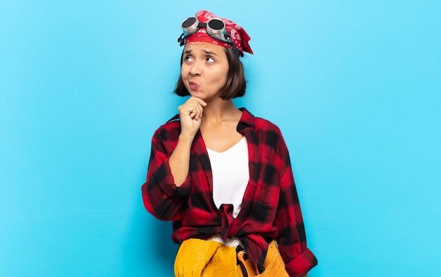 Jeune femme latine pensant, se sentant dubitative et confuse, avec différentes options, se demandant quelle décision prendre
