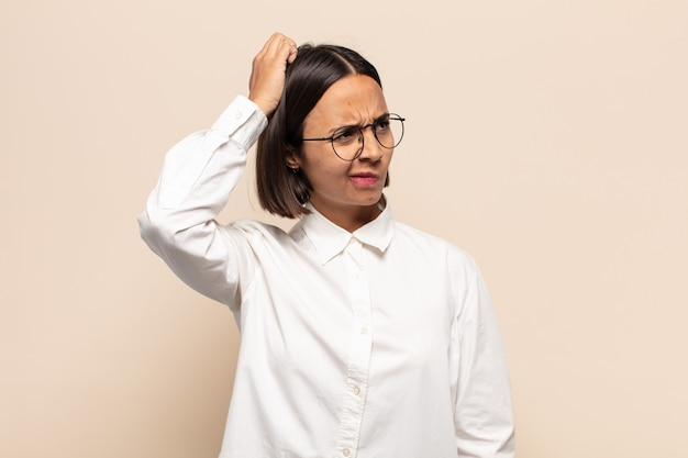 Jeune femme latine perplexe et confuse, se gratte la tête et regarde sur le côté