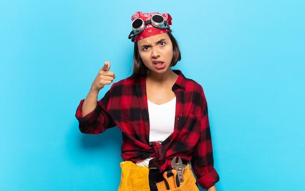 Jeune femme latine pointant la caméra avec une expression agressive en colère ressemblant à un patron furieux et fou