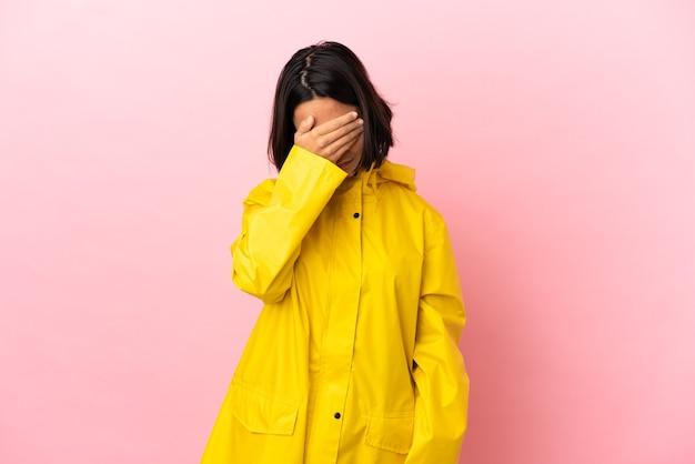 Jeune femme latine portant un manteau imperméable sur fond isolé avec une expression fatiguée et malade