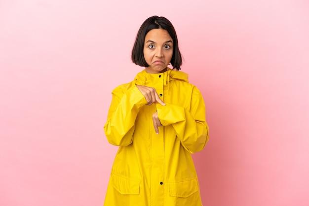 Jeune femme latine portant un manteau imperméable sur fond isolé faisant le geste d'être en retard