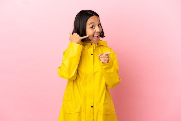 Jeune femme latine portant un manteau imperméable sur fond isolé faisant un geste de téléphone et pointant vers l'avant