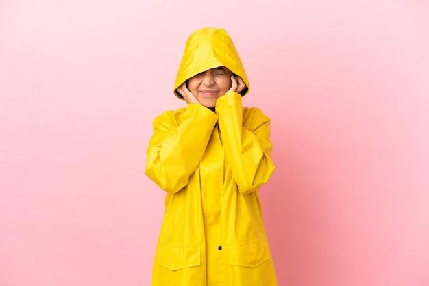 Jeune femme latine portant un manteau imperméable sur fond isolé frustré et couvrant les oreilles