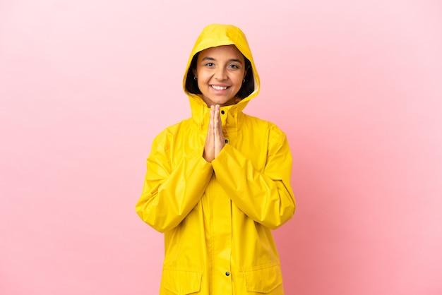 Jeune femme latine portant un manteau imperméable sur fond isolé maintient la paume ensemble. la personne demande quelque chose