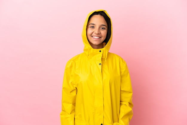 Jeune femme latine portant un manteau imperméable sur fond isolé en riant
