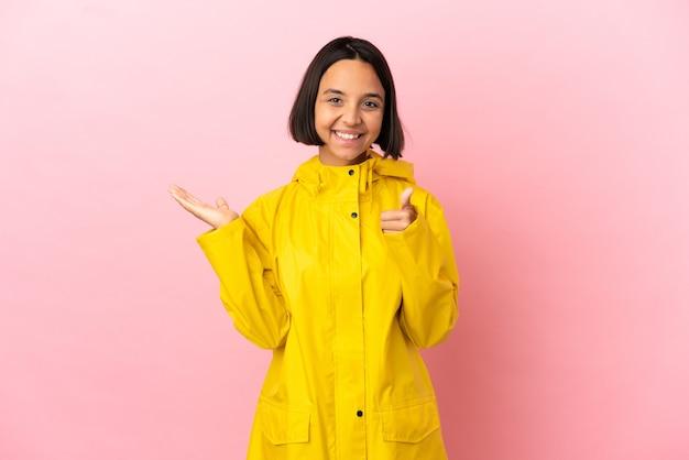 Jeune femme latine portant un manteau imperméable sur fond isolé tenant un espace de copie imaginaire sur la paume pour insérer une annonce et avec les pouces vers le haut