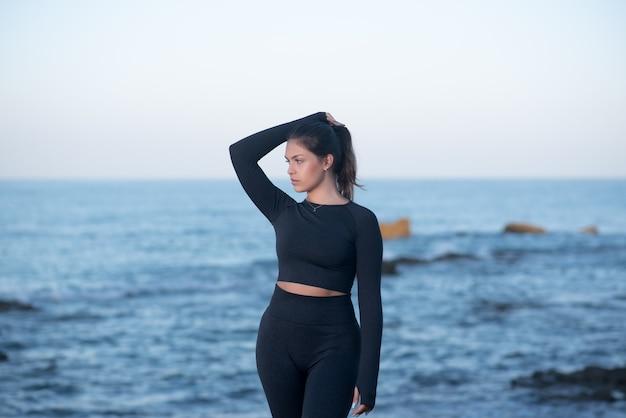 Jeune femme latine portant des vêtements d'entraînement noirs, debout sur la plage et posant