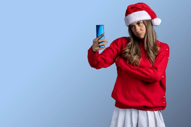 Jeune femme latine portant des vêtements de noël faisant un appel vidéo ennuyeux