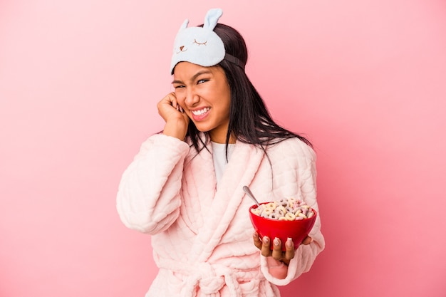 Jeune femme latine en pyjama tenant un bol de céréales isolé sur fond rose couvrant les oreilles avec les mains.