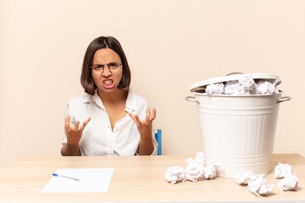 Jeune femme latine à la recherche de colère, agacée et frustrée hurlant wtf ou quel est le problème avec vous