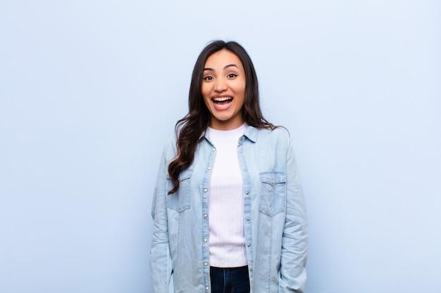 Jeune femme latine à la recherche de plaisir et agréablement surpris, excité par une expression fascinée et choquée sur un mur plat