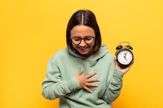 Jeune femme latine riant aux éclats d'une blague hilarante, se sentant heureuse et joyeuse, s'amusant