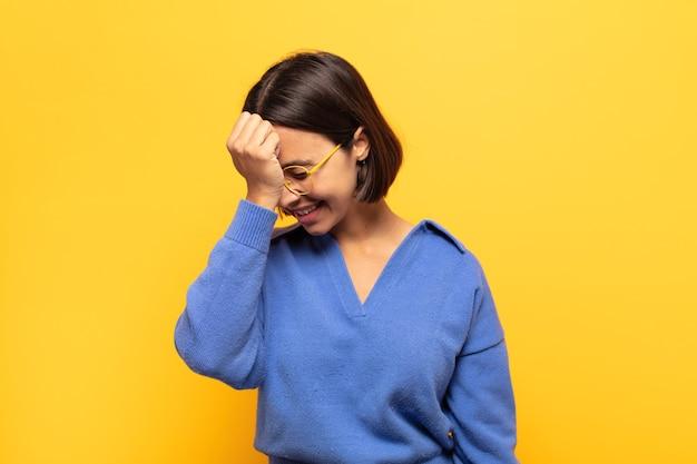 Jeune femme latine riant et giflant le front comme pour dire d'oh ! j'ai oublié ou c'était une erreur stupide