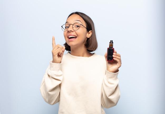 Jeune femme latine se sentant comme un génie heureux et excité après avoir réalisé une idée, levant joyeusement le doigt, eureka!