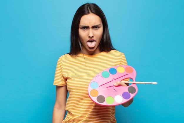 Jeune femme latine se sentant dégoûtée et irritée, tirant la langue, n'aimant pas quelque chose de méchant et dégueulasse
