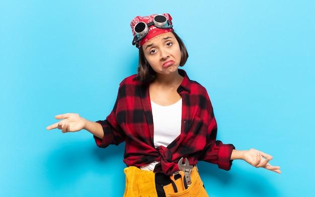 Jeune femme latine se sentant désemparée et confuse, n'ayant aucune idée, absolument perplexe devant un regard stupide ou stupide