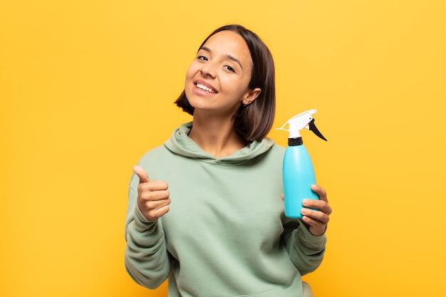 Jeune femme latine se sentant fière, insouciante, confiante et heureuse, souriant positivement avec le pouce levé