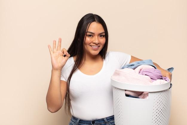 Jeune femme latine se sentant heureuse, détendue et satisfaite, montrant son approbation avec un geste correct, souriant