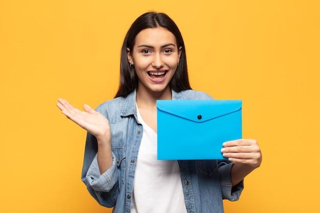 Jeune femme latine se sentant heureuse, excitée, surprise ou choquée, souriante et étonnée de quelque chose d'incroyable