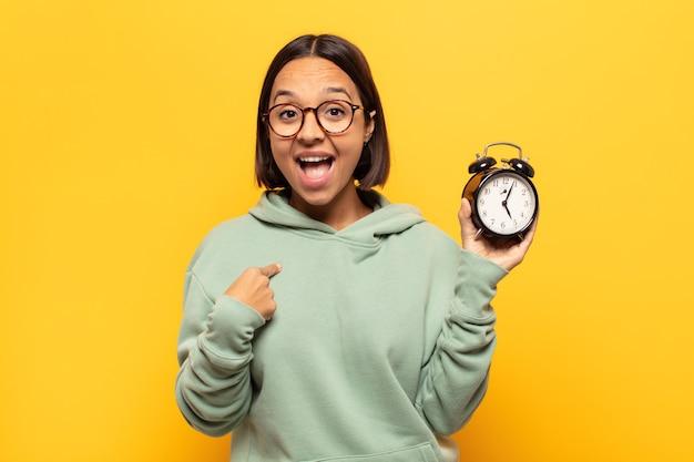 Jeune femme latine se sentant heureuse, surprise et fière, pointant vers soi avec un regard excité et étonné
