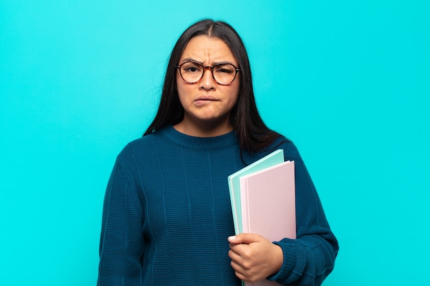 Jeune femme latine se sentant ignorante, confuse et incertaine quant à l'option à choisir, essayant de résoudre le problème