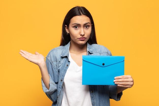 Jeune femme latine se sentant perplexe et confus, doutant, pondérant ou choisissant différentes options avec une expression drôle
