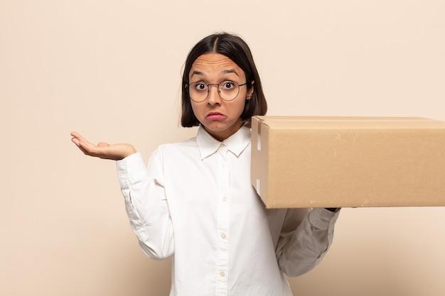 Jeune femme latine se sentant perplexe et confuse, doutant, pondérant ou choisissant différentes options avec une expression amusante
