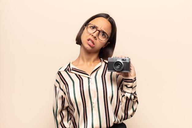 Jeune femme latine se sentant perplexe et confuse, avec une expression stupide et abasourdie en regardant quelque chose d'inattendu