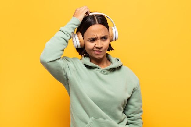 Jeune femme latine se sentant perplexe et confuse, se grattant la tête et regardant sur le côté