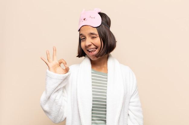 Jeune femme latine se sentant réussie et satisfaite, souriant avec la bouche grande ouverte, faisant signe avec la main