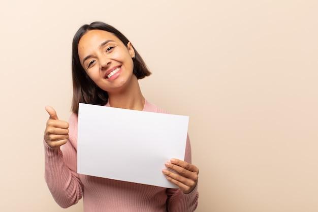 Jeune femme latine se sentir fière, insouciante, confiante et heureuse, souriant positivement avec les pouces vers le haut