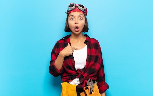Jeune femme latine semblant choquée et surprise avec la bouche grande ouverte, pointant vers soi