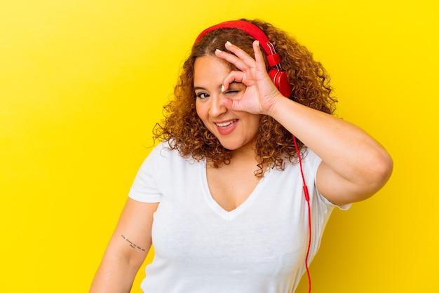 Jeune femme latine sinueuse écoute de la musique isolée sur fond jaune excité en gardant le geste ok sur les yeux.