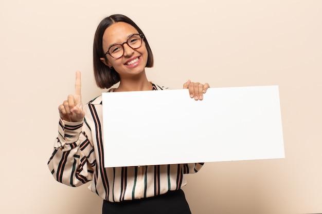 Jeune femme latine souriant fièrement et avec confiance en faisant le numéro un pose triomphalement, se sentant comme un leader
