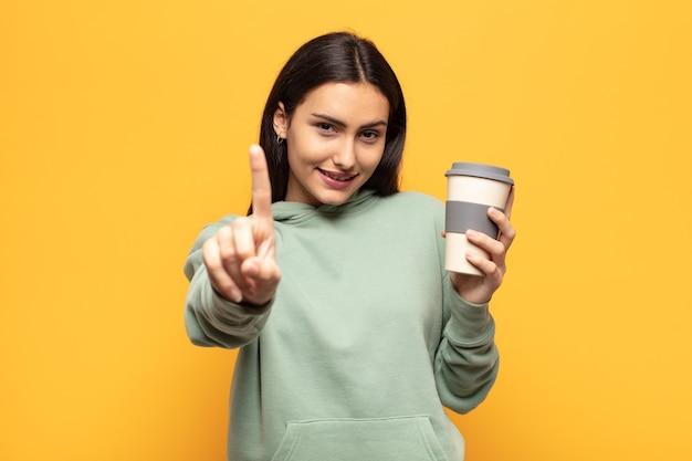 Jeune femme latine souriant fièrement et en toute confiance faisant le numéro un pose triomphalement, se sentant comme un leader