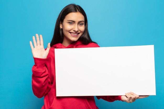 Jeune femme latine souriant joyeusement et gaiement, en agitant la main, en vous accueillant et en vous saluant, ou en vous disant au revoir