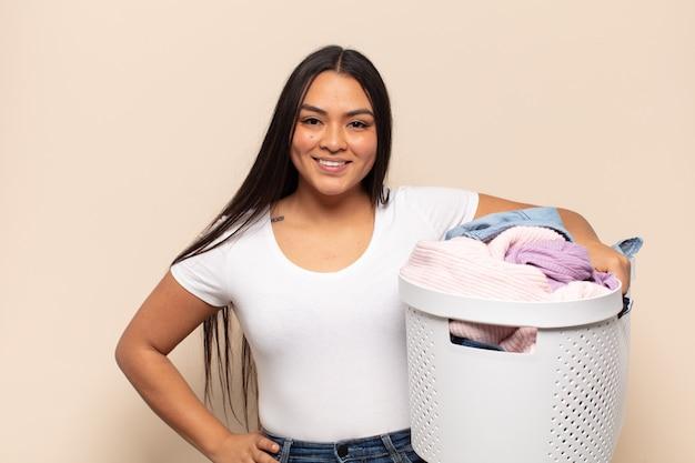 Jeune femme latine souriant joyeusement avec une main sur la hanche et une attitude confiante, positive, fière et amicale