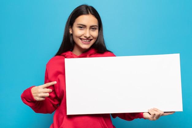 Jeune femme latine souriant joyeusement, se sentant heureux et pointant vers le côté et vers le haut