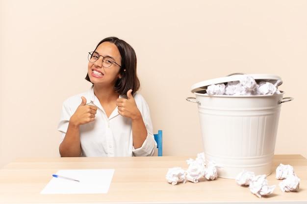Jeune femme latine souriant largement à la recherche de bonheur, positif, confiant et réussi, avec les deux pouces vers le haut