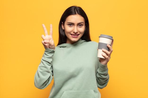 Jeune femme latine souriant et à la sympathique, montrant le numéro deux ou seconde avec la main en avant, compte à rebours