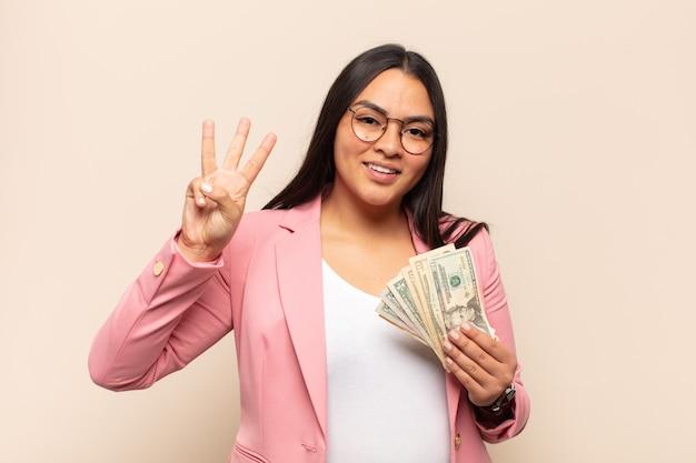 Jeune femme latine souriant et à la sympathique, montrant le numéro trois ou troisième avec la main en avant, compte à rebours