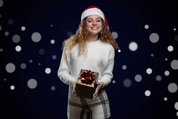 Jeune femme latine souriante, célébrant noël avec un cadeau dans ses mains et un chapeau de père noël.