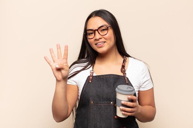 Jeune femme latine souriante et à la convivialité, montrant le numéro quatre ou quatrième avec la main en avant, compte à rebours